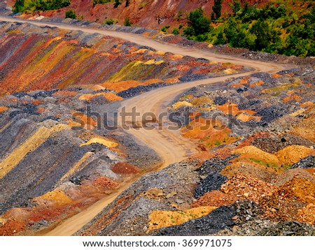 Road through dumps of depleted metal ore - stock photo