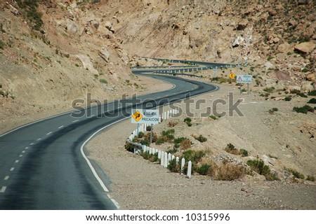 Road through mountainous dryland - stock photo
