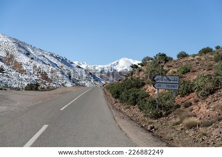 Road through snow covered Atlas mountains in Morocco - stock photo