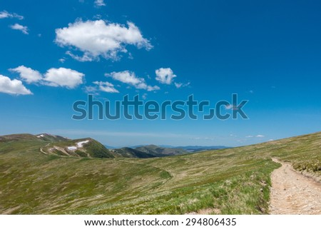 Road through the amazing spring mountain under blue sky with white clouds - Svydovets range, Carpathians, West Ukraine - stock photo