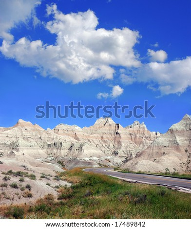 Road through the badlands in South Dakota with a cloudy sky. - stock photo