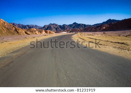 Road through the desert and sandy hills - stock photo