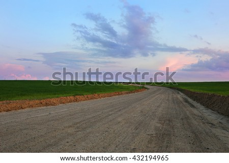 Road through the green field and clouds on blue sky in summer day. Road in a field. Belarus - stock photo