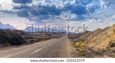 road through the stony desert going to a distance, mountain tops on the horizon, dark thunderclouds in the sky
