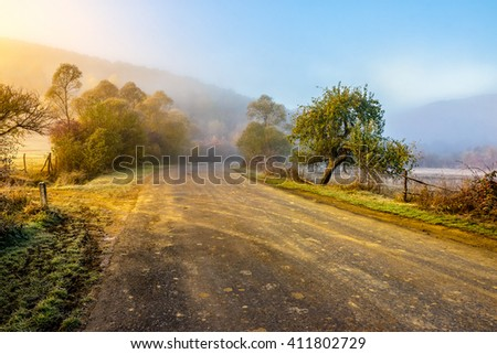 road through the valley near the forest in foggy mountains at hot sunrise