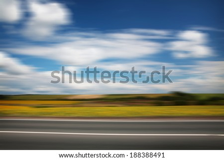 Road through the yellow sunflower field with clouds on blue sky motion blur - stock photo