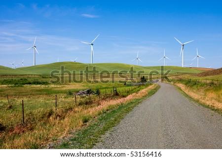 Road through wind turbines farm - stock photo