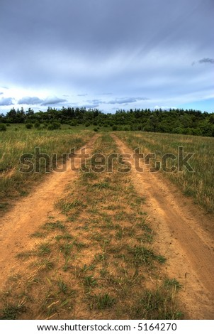 Road to a field. The drama sky above a wood - stock photo