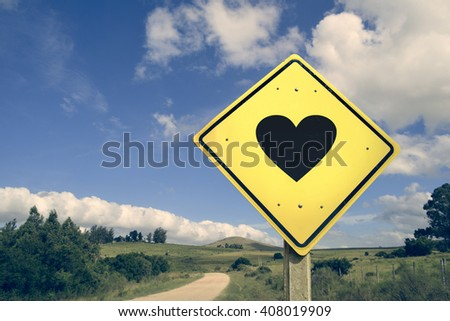 Road to love heart concept icon traffic sign on empty countryside nature landscape, vintage filter effect. - stock photo