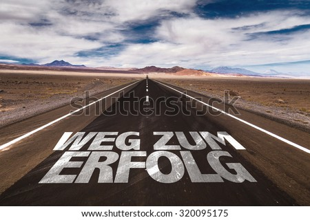 Road to Success (in German) written on desert road - stock photo