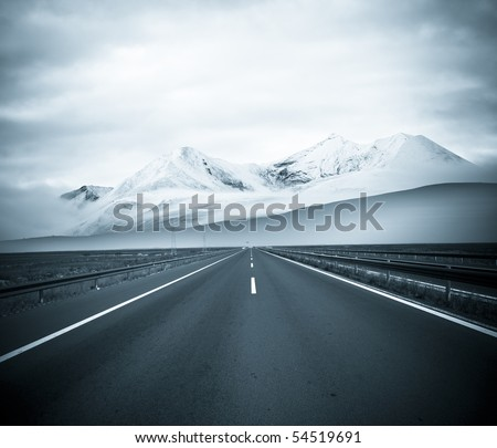 road to the future with the mountain and blue sky background outdoor. - stock photo