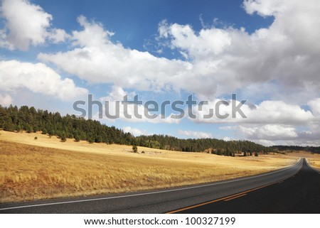Road to the Grand Canyon. Autumn yellow fields and the magnificent cloudy sky - stock photo