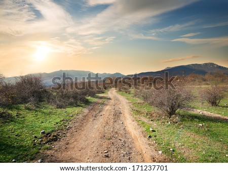 Road to the mountains on a clear autumn evening - stock photo