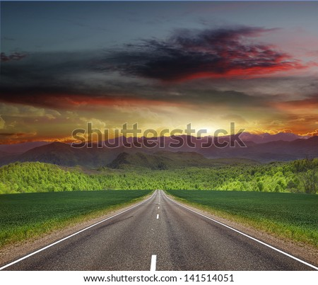Road to the mountains through a field of young wheat - stock photo