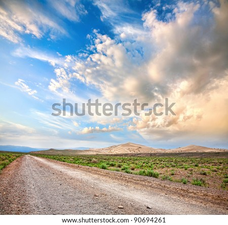 Road to the mountains through the desert at dramatic cloudy sky background - stock photo