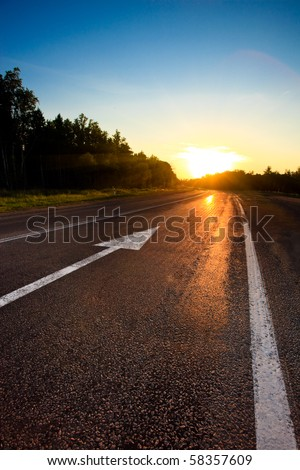 road to the sunset with arrow on asphalt - stock photo
