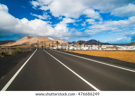 Road to Yaiza white houses village under volcanic mountains.  Lanzarote. Canary Islands. Spain