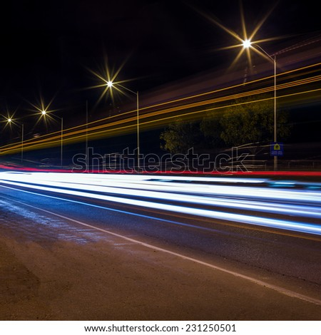 Road traffic and light trails at night  - stock photo