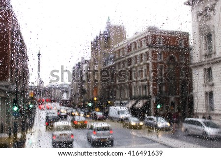 road traffic in London on a rainy day through the bus window. raindrops and blurred urban scene from the glass window of the bus. - stock photo