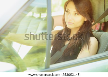 Road transportation. Beautiful young woman driver driving a car. Attractive brunette going on a trip travel. - stock photo