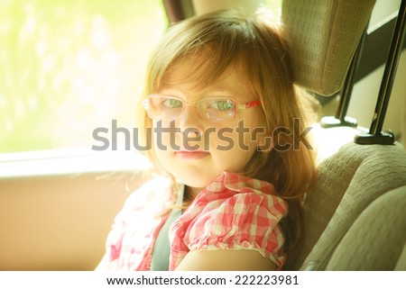 Road transportation. Little girl child kid in eyeglasses sitting in the back of car and going on a trip travel. - stock photo