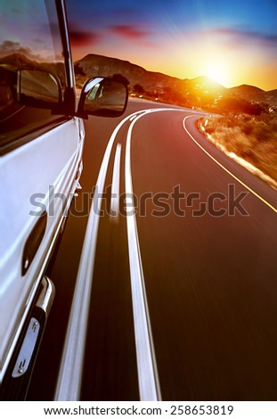 Road trip, car on the highway, road trip on sunset, journey and freedom travel, slow motion photo - stock photo