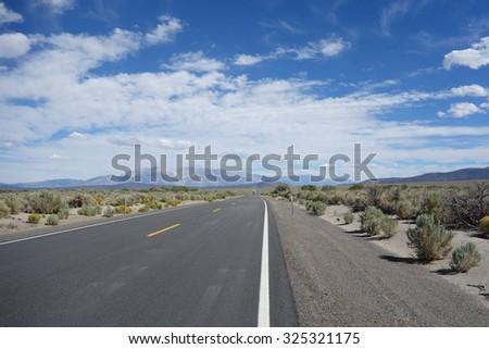 road trip from yosemite to las vegas via nevafa desert. blue sky with straight highway look amazing - stock photo