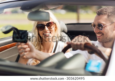 road trip, leisure, travel, technology and people concept - happy man and woman driving car and using gps navigation system - stock photo