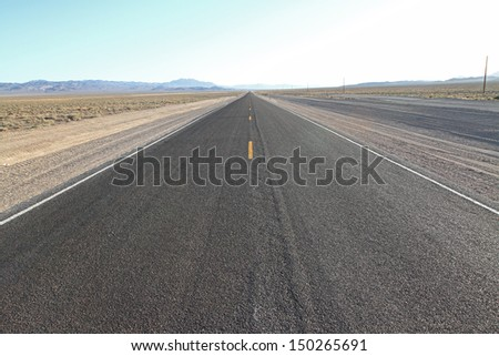 Road Trip on infinite roads through the wilderness - stock photo