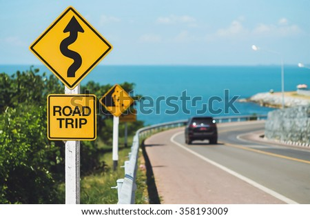 road trip word and curvy road sign - stock photo