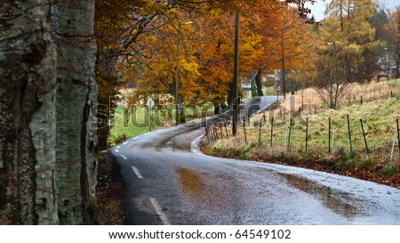 Road trough norwegian country road in rainy weather - stock photo