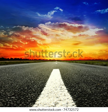 Road vanishing to the horizon under sun rays coming down trough the dramatic stormy clouds - stock photo