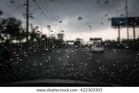 Road view through car window blurry with heavy rain, Driving in rain, rainy weather - stock photo