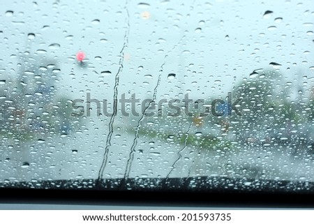Road view through car window with rain drops  - stock photo