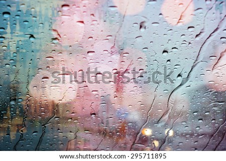 Road view through car window with rain drops and light bokeh. - stock photo