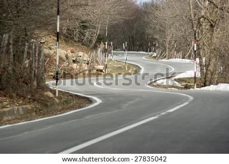 Road winding mountain crosses the wood - stock photo