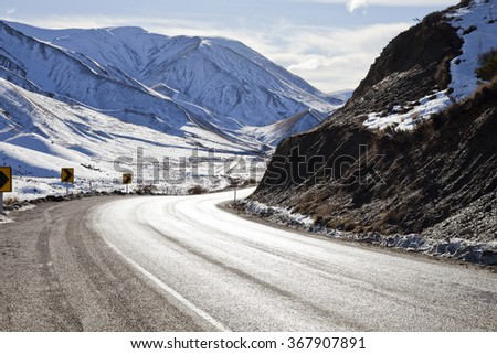 Road winding through a snow covered Lewis Pass, Canterbury, South Island, New Zealand - stock photo