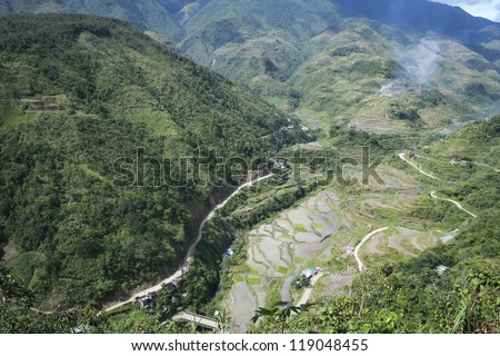road winding through steep valleys of the mountain province of banaue in luzon philippines past flooded traditional rice terraces - stock photo