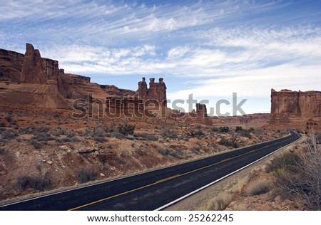 Road winds through Arches National Park near the 3 Gossips. - stock photo