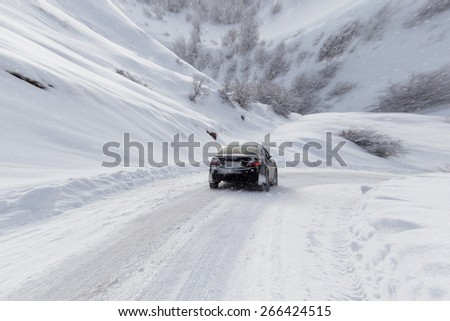 road with a car in winter in the mountains - stock photo