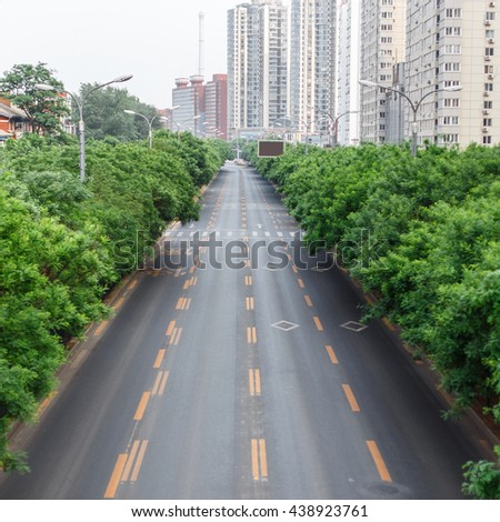 Road with a marking. The track on the background of the city and trees. - stock photo