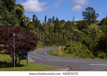 Road with a red car near Waitomo Caves - stock photo