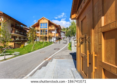 Road with alpine houses in San Cassiano mountain village on sunny summer day, Dolomites Mountains, Italy - stock photo