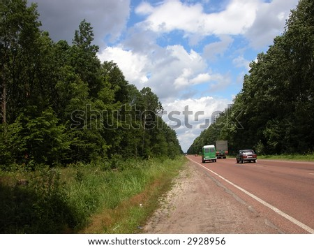 Road with cars in green forest. Ukraine. Sky with clouds.