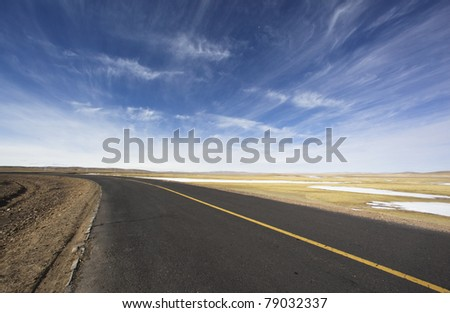 road with cloudscape on the altiplano in the northwest of china - stock photo