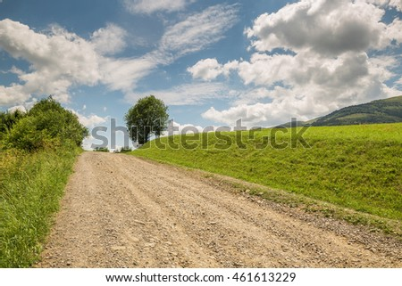 road with gravel stretches up the green hill