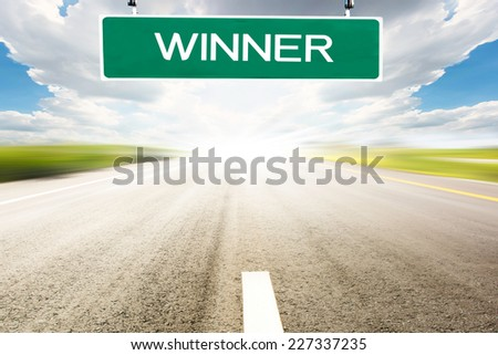 "Road with highway sign to ""WINNER"" representing the concept of journey to a focused destination resulting to success - stock photo"