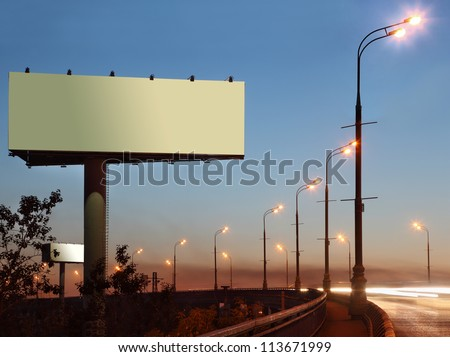 Road with lanterns and large blank billboard at evening in city. - stock photo
