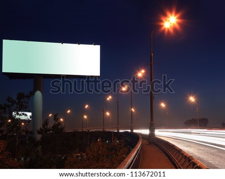 Road with lights and large blank billboard at dark night in city. - stock photo