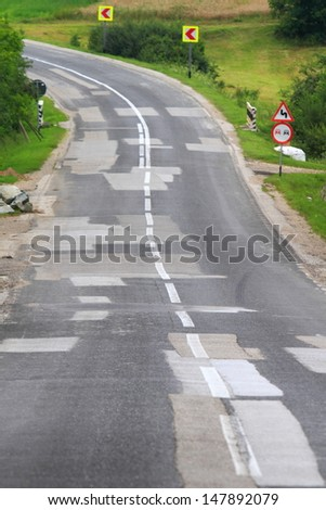 Road with many patches in different shades of gray  - stock photo